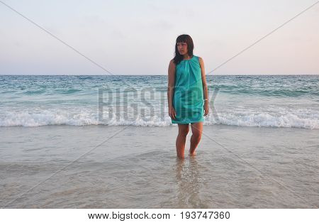 beautiful brunette girl in a short green sundress with a smooth southern sun on the sea background. legs washed by the surf. evening on the beach