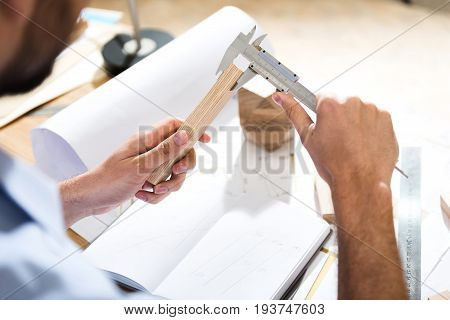 Accuracy in everything. Close up top view of hands of bearded carpenter is measuring value of wooden plank with calipers while sitting at table in workshop. Selective focus