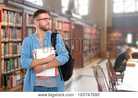 A male student with a school bag holding books in library .