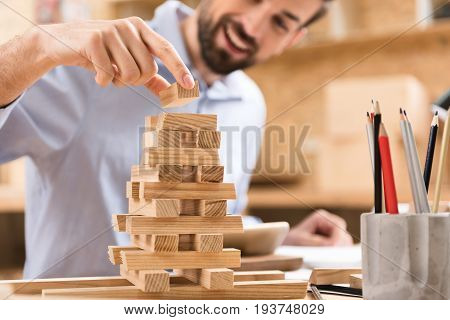Take pleasure in game. Close-up of miniature of pyramid from small wooden play planks. Cheerful pleasant bearded woodworker is building sample with smile while resting in his workshop. Selective focus