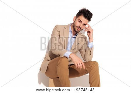 pensive man with hand on forehead looks at the camera while sitting on white background