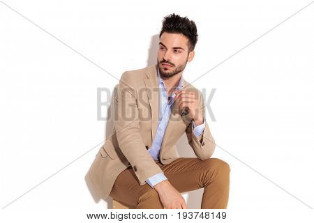 side view of a pensive young business man looking away from the camera while sitting in studio