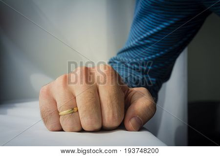 Man With A Wedding Ring Squeezed His Hand On White Cloth Background