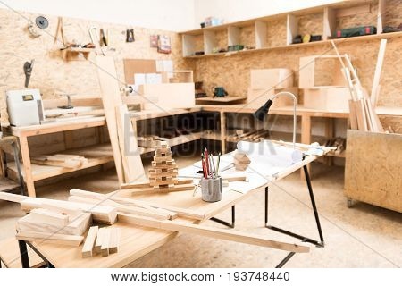 Woodworking workshop of carpenter. Workbench with planks and colored pencils and sketches on foreground. Wood cutting stand with various professional tools are on background. Selective focus