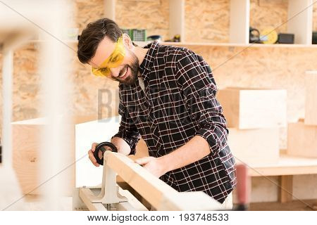 Do it yourself. Assiduous young woodworker wearing safety glasses is working with wood lathe in spacious workshop. He is laboring with smile