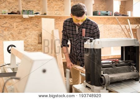 Difficult process. Serious young woodworker in safety glasses is holding wooden bar and working on thickness planer with concentration. Focus on man. Copy space in the left side
