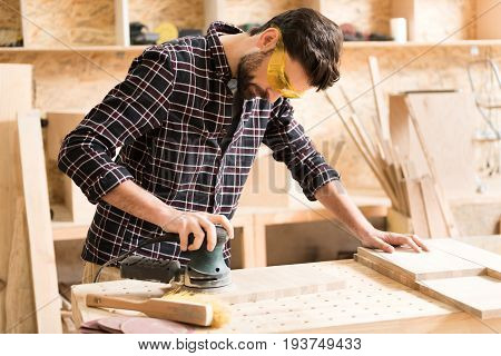 Involved in working process. Pleasant bearded young woodworker wearing safety glasses is using hand-held sander while polishing wooden plank in spacious workshop