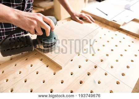 Woodworking process. Close-up top view of hands of carpenter, which is using hand-held sander and polishing wooden plank in workshop. Copy space in the right side
