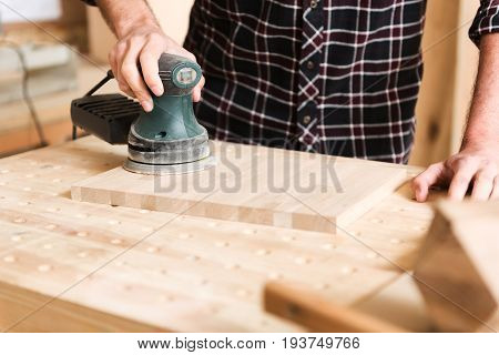 Make it good. Close-up of hands of woodworker, which is using hand-held sander and grinding wooden board while leaning on table