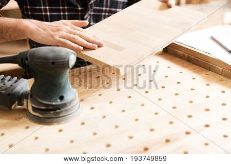 Well done. Close up of hands of joiner which is touching wooden plank while checking result of his work. Hand-held sander is on foreground. Selective focus with copy space in the right side