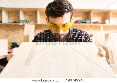 Perfect job. portrait of pleasant young carpenter in protective glasses is gazing at wooden board and smiling while holding it close to face