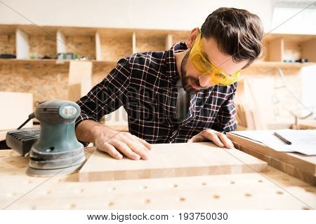 Work with concentration. Diligent young bearded carpenter wearing protective glasses is touching wooden plank while checking its smoothness. Hand-held sander is near board