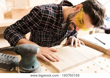 Excellent work. Positive young bearded woodworker wearing safety glasses is leaning over board while touching it with smile. Hand-held sander is near plank