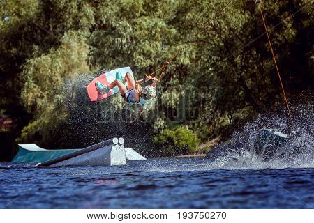 Woman is an extreme in a jump over the water. She trains before the performance.