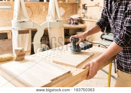 Working atmosphere. Close-up of arms of craftsman with instrument. Energetic carpenter is using hand-held sander and polishing wooden plank in workshop. Copy space in the left side
