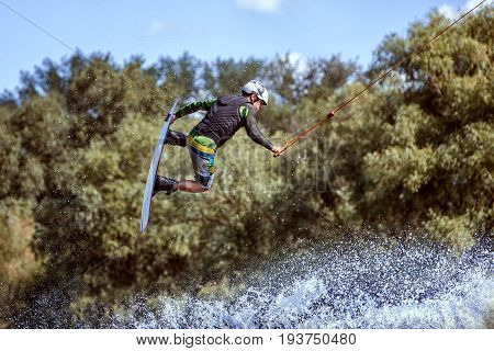 Wakeboarder sportsman jumping in a water park during training.