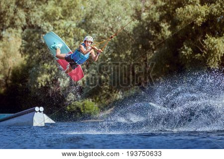 Professional athlete during a wakeboard trick on the water.