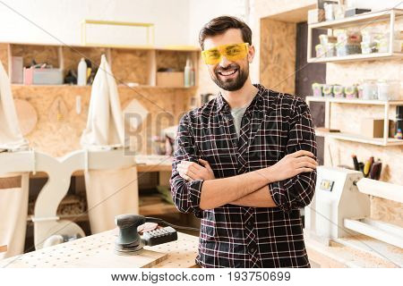 Happy at work. Portrait of cheerful young bearded woodworker wearing safety glasses is standing at workshop with crossed arms and looking at camera with joy. Professional equipment on background