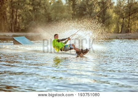 Guy rushes along the lake on the board extreme sport wakeboarding.