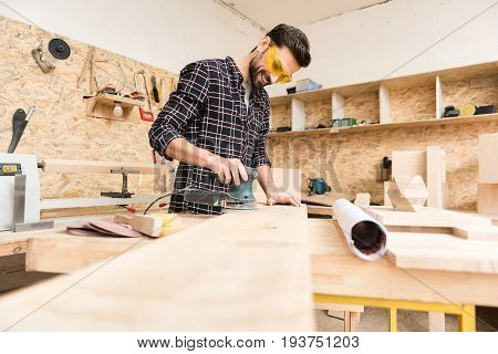 Inspired by work. Low angle of joyful pleasant bearded woodworker wearing protective glasses is standing with hand-held sander and polishing wooden plank