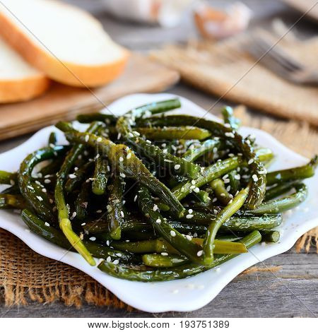 Crispy garlic stalks. Fried green garlic stalks with spices and sesame seeds on a white plate. Rustic style. Unusual veggie food. Closeup