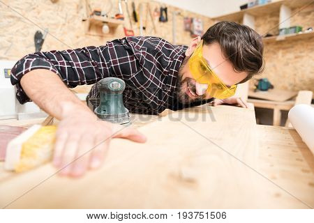 Good work. Skilled carpentry craftsman in safety glasses is gazing at plank expertly and checking it for quality while standing in his workshop with professional equipment on background