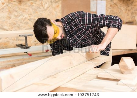 Checking accuracy. Young concentrated bearded woodworker wearing safety glasses is measuring width of wooden bar using calipers