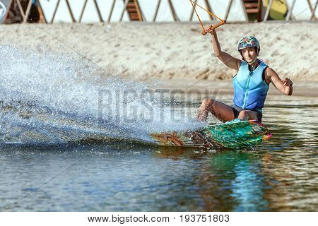 Woman is an extreme sportswoman on a wakeboard on the water.