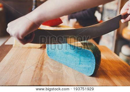Cutting gouda pesto lavender in grocery shop. Cuttign blue cheese wheel with two-handed knife, closeup