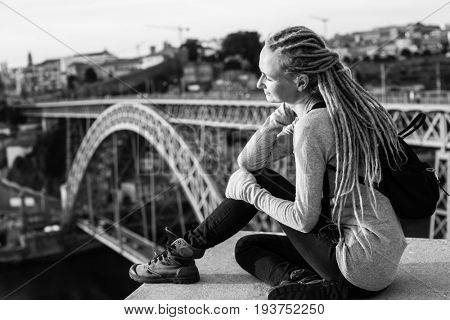 Black and white photo of young woman with dreadlocks sitting on the background of the Dom Luis I bridge in Porto, Portugal.