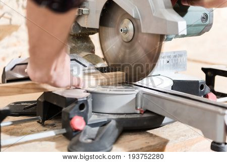 Specialized instrument. Close up of radial arm saw in action. Carpenter is holding wooden bar and operating on tool. Selective focus