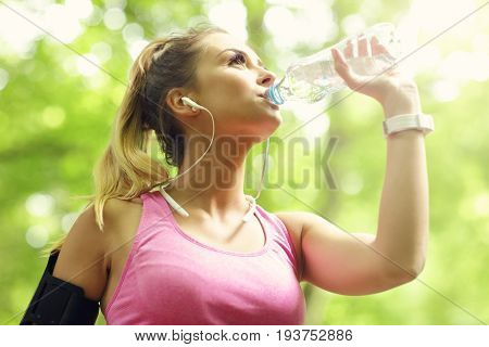 Woman jogging in the forest with bottle of water