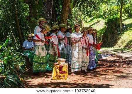 Ivoloina Madagascar - December 22 2015: Folk Song Ensemble are preparing to sing in the park of Ivoloina near the city of Toamasina (Tamatave) Madagascar. Flower petals on the ground.
