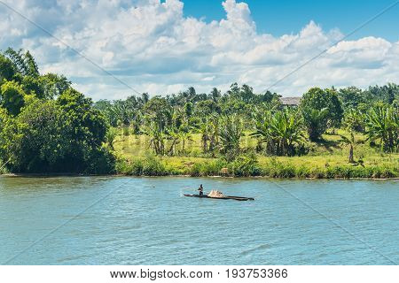 Ivoloina Madagascar - December 22 2015: Malagasy countryside man from village transport freight by Traditional handmade dugout wooden boat near the city of Toamasina (Tamatave) Madagascar East Africa. Everyday life on the river.