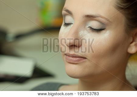 Visage cosmetics concept. Woman with full make up closeup powder dust on cheeks baking method