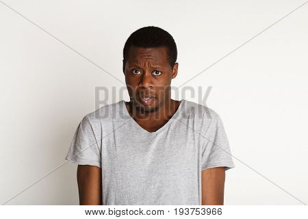 Negative emotions. Black man expressing fear and hesitation, standing on white background, studio shot