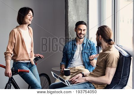 Cheerful female freelancer is leaning against bicycle and looking at her male colleagues. They are talking about certain task