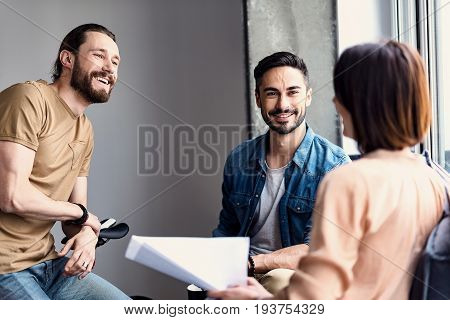 Hilarious freelancer is leaning against bicycle and looking at colleagues with bright smile. They are discussing ideas