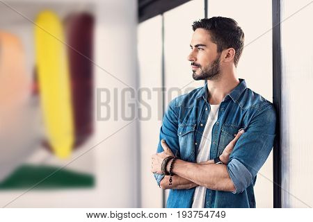 Mindful freelancer is standing in office and attentively looking ahead. He crossing his hands. Copy space on left side