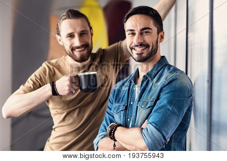 Hilarious freelancer is standing in office near wall and looking at camera with sincere smile. Colleague is holding cup of beverage. Portrait
