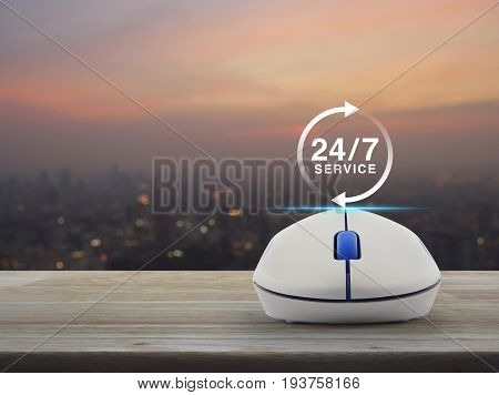 24 hours service icon with wireless computer mouse on wooden table over blur of cityscape on warm light sundown Full time service concept
