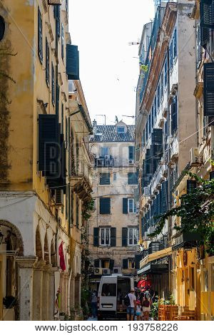 Narrow streets of Corfu island, Greece. Old and ramshackle buildings on sides and a working car