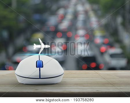 Airplane icon with wireless computer mouse on wooden table over blur of rush hour with cars and road Business transportation concept
