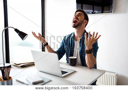Yelling man is sitting near table. He rising hands and looking up with cry