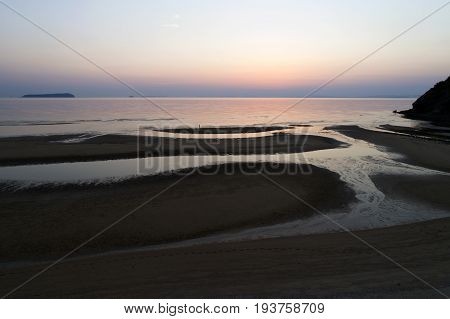 Aerial view of calm ocean at sunset, beautiful evening sky with reflected in calm sea water