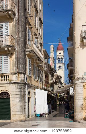 Narrow streets of Corfu island, Greece. Old and ramshackle buildings on sides and a clobk