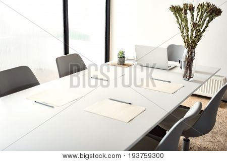 Minimalistic atmosphere for successful work. Open laptop is near glassful vase with odd flowers