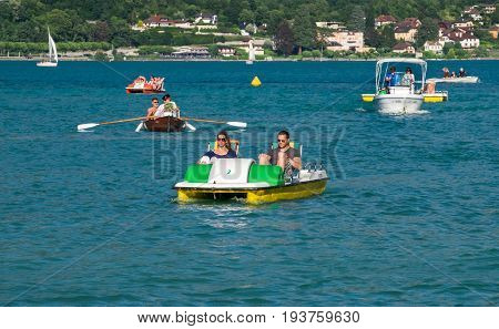 ANNECY FRANCE - JUNE 17 2017: People ride on pedal boats or paddle boats at Lake Annecy at Haute-Savoie department. France