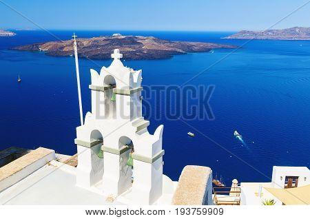 Two bell towers of Oia, Santorini, Greece with caldera at the background