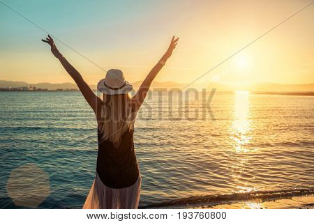Blonde woman in summer hat stay on the coastline by the sea beach. Sea sunset view. Freedom. Wind. Summer. Beach. Sunset. Vacation. Looking to a sky and sea. Looking forward.